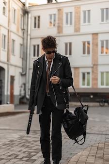 Il giovane hipster bello in occhiali da sole in camicia in un'elegante giacca di pelle nera con zaino fuma vicino agli edifici della città. modello di moda ragazzo cool con sigaretta all'aperto. stile americano.