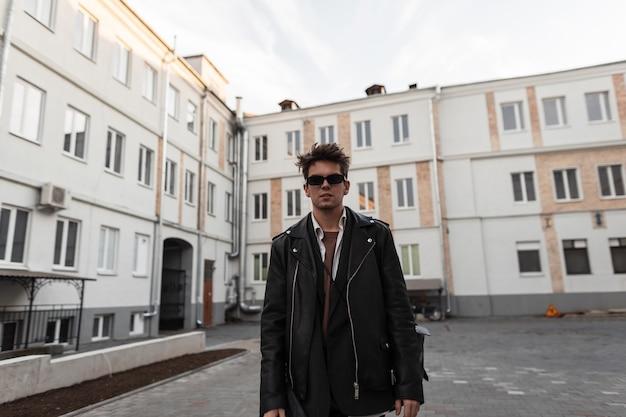 Il giovane hipster bello in occhiali da sole con l'acconciatura in una camicia vintage in un'elegante giacca di pelle nera si trova vicino agli edifici nel cortile. modello di moda ragazzo cool all'aperto. stile americano.