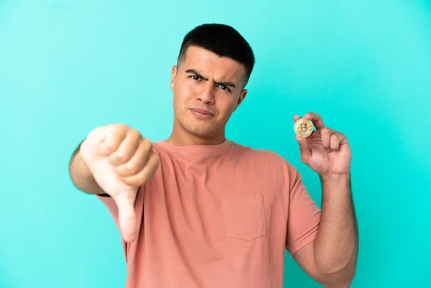 Giovane uomo bello che tiene un bitcoin su sfondo blu isolato che mostra il pollice verso il basso con espressione negativa