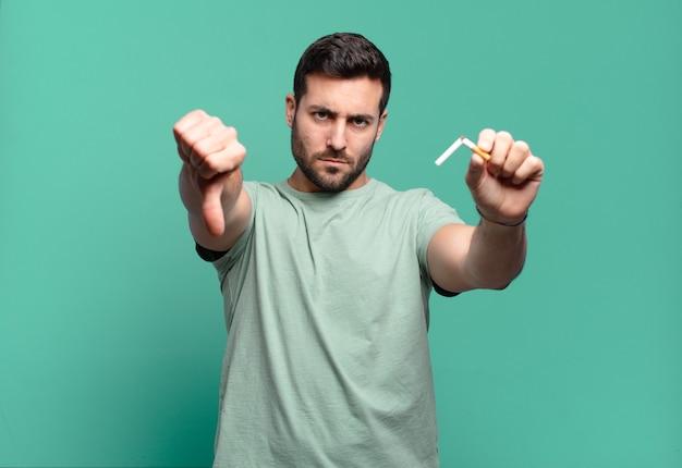 Giovane uomo bello che tiene una sigaretta. smettere di fumare concetto smoking