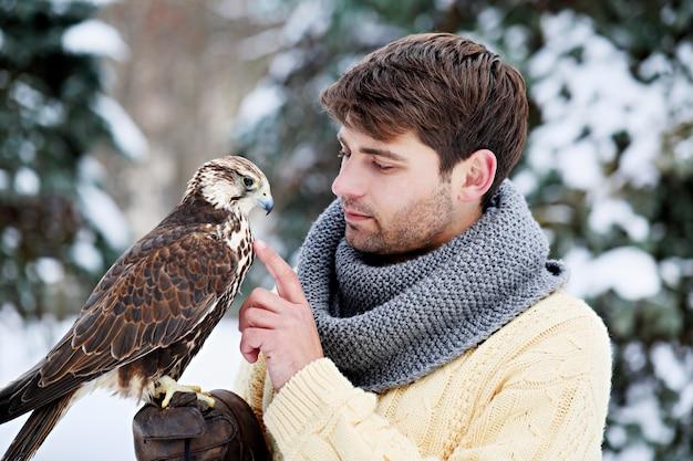 Giovane uomo bello che tiene un falco sul braccio
