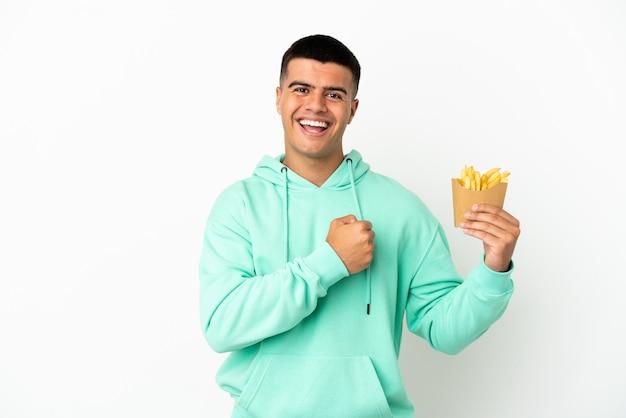 Giovane uomo bello che tiene patatine fritte su sfondo bianco isolato che celebra una vittoria