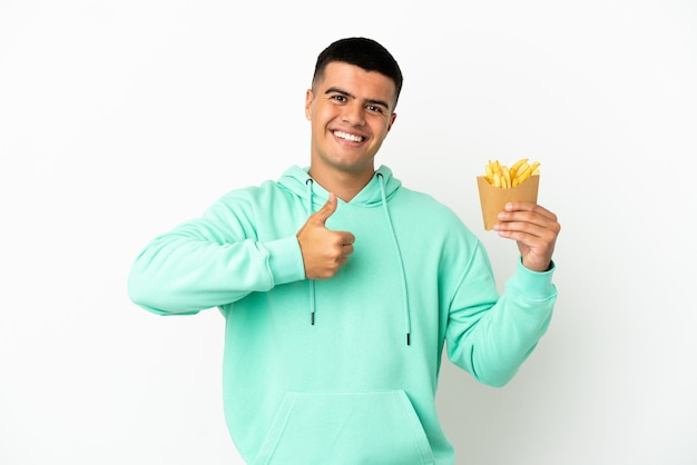 Giovane uomo bello che tiene patatine fritte su sfondo bianco isolato dando un gesto di pollice in alto