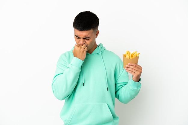 Giovane uomo bello che tiene patatine fritte su sfondo bianco isolato avendo dubbi