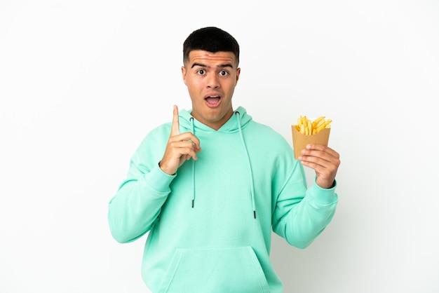 Giovane uomo bello che tiene patatine fritte su sfondo bianco isolato con l'intenzione di realizzare la soluzione mentre si solleva un dito