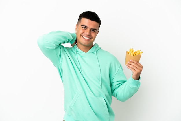 Giovane uomo bello che tiene patatine fritte su sfondo bianco isolato ridendo