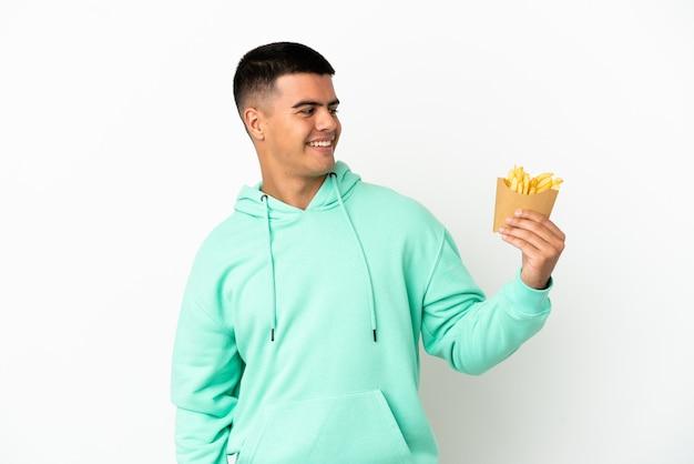 Giovane uomo bello che tiene patatine fritte su sfondo bianco isolato guardando di lato e sorridente