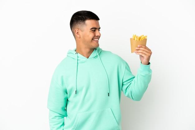 Giovane uomo bello che tiene patatine fritte su sfondo bianco isolato guardando lato
