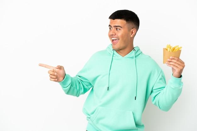 Giovane uomo bello che tiene patatine fritte su sfondo bianco isolato che punta il dito di lato e presenta un prodotto