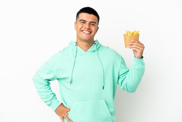 Giovane uomo bello che tiene patatine fritte su sfondo bianco isolato in posa con le braccia all'anca e sorridente