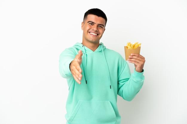 Giovane uomo bello che tiene patatine fritte su sfondo bianco isolato che stringe la mano per chiudere un buon affare