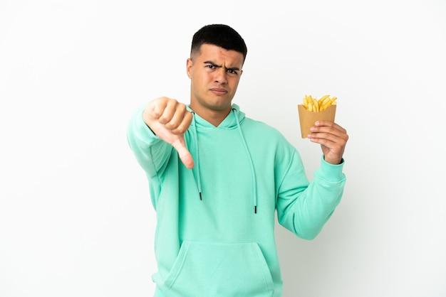 Giovane uomo bello che tiene patatine fritte su sfondo bianco isolato che mostra pollice giù con espressione negativa