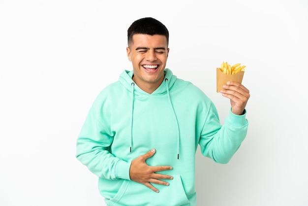 Giovane uomo bello che tiene patatine fritte su sfondo bianco isolato sorridendo molto