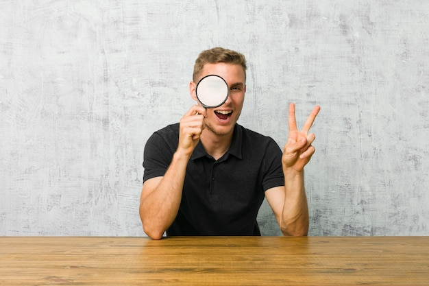 Giovane uomo bello che tiene una lente d'ingrandimento che mostra il segno di vittoria e che sorride ampiamente.