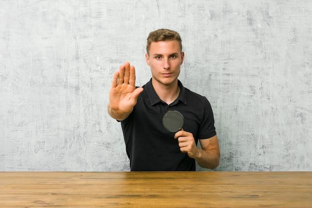 Giovane uomo bello che tiene una lente d'ingrandimento in piedi con la mano tesa che mostra il segnale di stop, impedendoti.