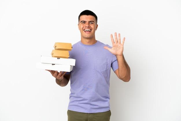 Giovane uomo bello che tiene pizze e hamburger su sfondo bianco isolato contando cinque con le dita