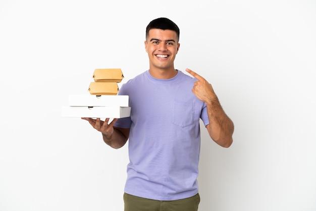 Giovane uomo bello che tiene pizze e hamburger su sfondo bianco isolato dando un gesto di pollice in alto