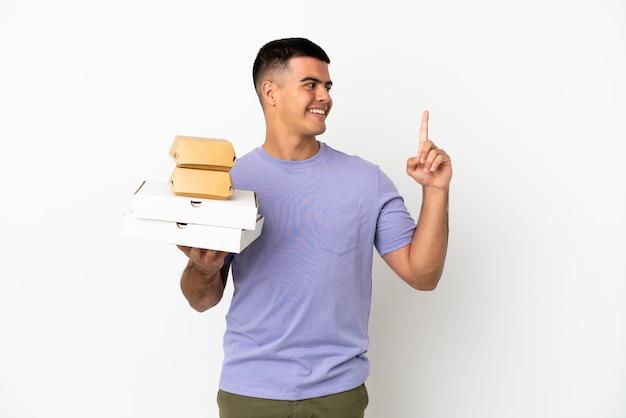 Giovane uomo bello che tiene pizze e hamburger su sfondo bianco isolato che punta verso l'alto una grande idea