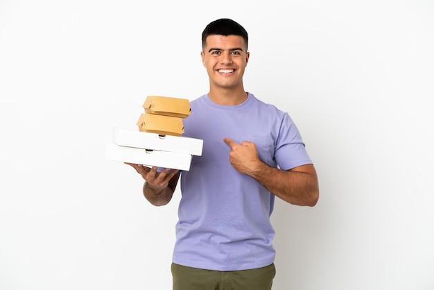 Giovane uomo bello che tiene pizze e hamburger su sfondo bianco isolato con espressione facciale a sorpresa