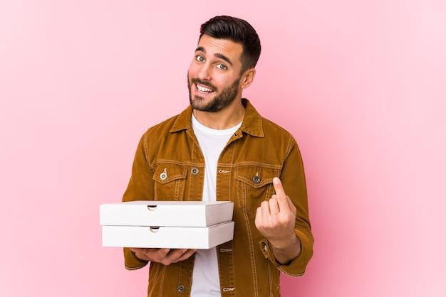 Giovane uomo bello che tiene pizze isolate puntando con il dito contro di te come se invitando ad avvicinarsi.