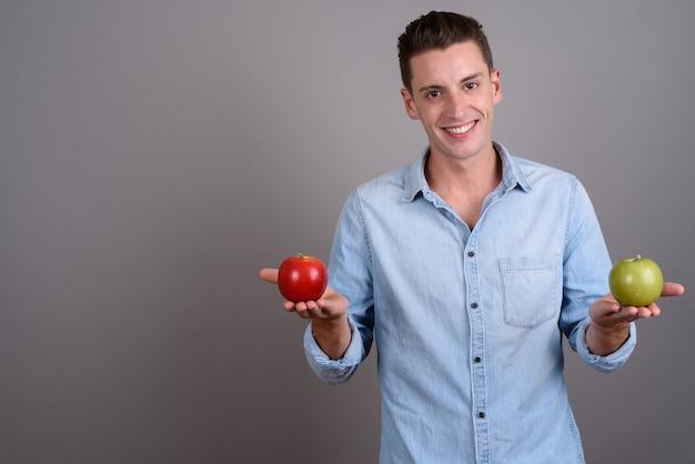 Giovane uomo bello che tiene mela rossa e mela verde su grigio