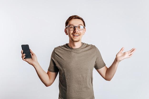 Giovane uomo bello che tiene uno smartphone e sorridente.