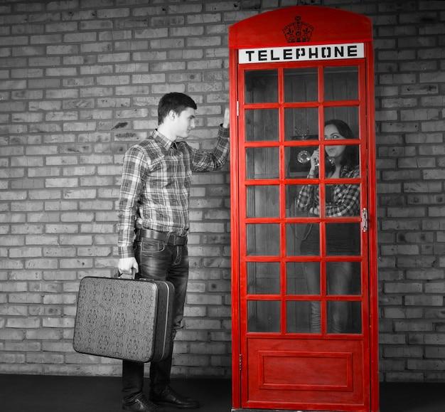 Giovane uomo bello che tiene la valigia che bussa alla cabina telefonica con una donna che parla all'interno. catturato con effetto scala di grigi.