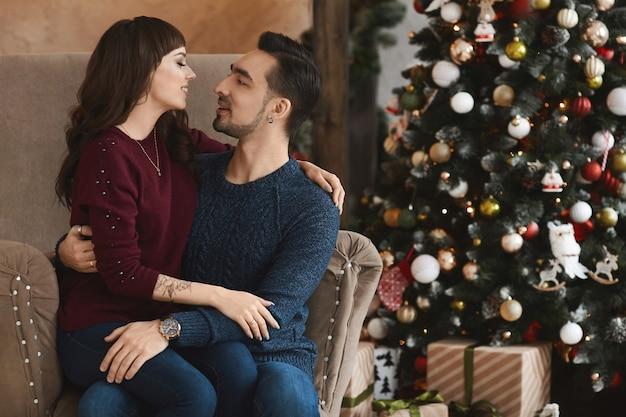 Giovane uomo bello abbraccia una ragazza bruna in poltrona in un salotto nel periodo natalizio