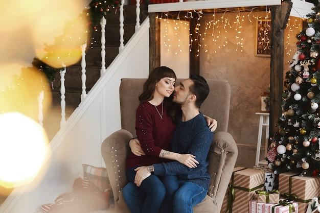 Giovane uomo bello abbraccia una ragazza bruna in poltrona in un soggiorno vicino all'albero di natale