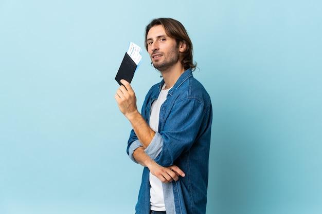 Giovane uomo bello isolato su blu felice in vacanza con passaporto e biglietti aerei