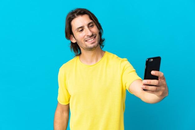 Giovane uomo bello isolato sull'azzurro che fa un selfie con il telefono cellulare