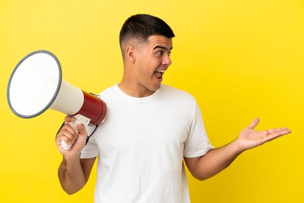 Giovane uomo bello su sfondo giallo isolato con in mano un megafono e con espressione facciale a sorpresa