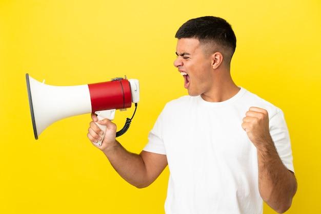 Giovane uomo bello su sfondo giallo isolato che grida attraverso un megafono per annunciare qualcosa in posizione laterale