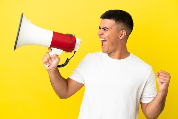 Giovane uomo bello su sfondo giallo isolato che grida attraverso un megafono per annunciare qualcosa in posizione laterale lateral