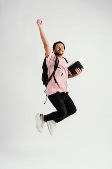 Giovane uomo bello che salta con lo zaino