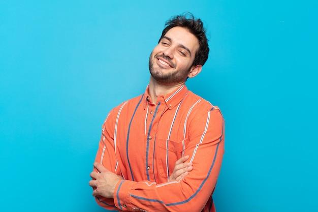 Giovane bell'uomo che ride felice con le braccia incrociate, con una posa rilassata, positiva e soddisfatta