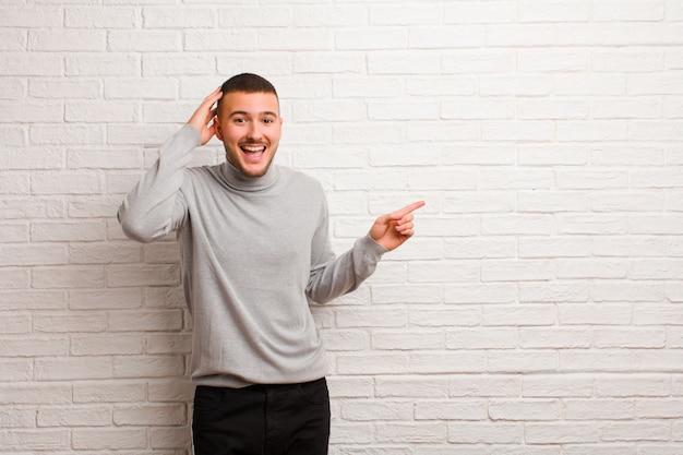 Giovane uomo bello che ride, che sembra felice, positivo e sorpreso, realizzando una grande idea che punta allo spazio laterale della copia contro la parete piana