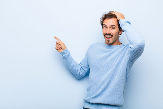 Giovane uomo bello che ride, che sembra felice, positivo e sorpreso, realizzando una grande idea che punta allo spazio laterale della copia isolato contro la parete piana