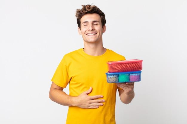 Giovane bell'uomo che ride ad alta voce per uno scherzo esilarante e tiene in mano scatole per il pranzo
