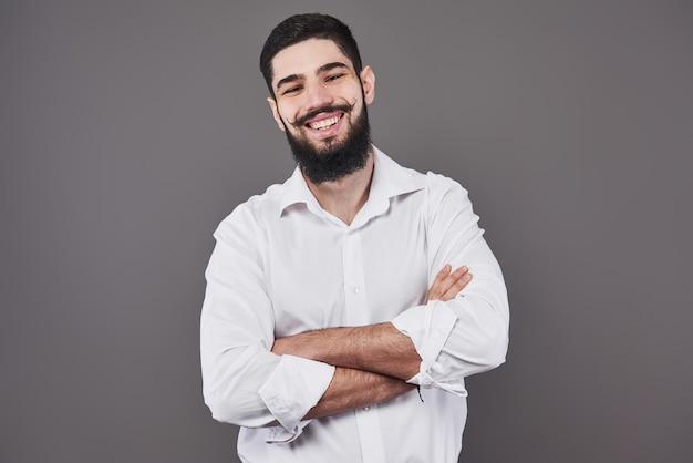 Giovane uomo bello che si appoggia contro il muro grigio con le braccia incrociate. un giovane serio con la barba guarda la telecamera. copia spazio.