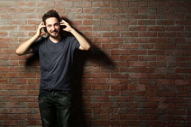 Musica d'ascolto del giovane uomo bello con le cuffie sul muro di mattoni