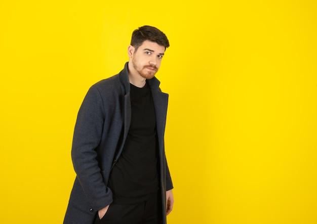 Giovane uomo bello che guarda la telecamera mentre ha le mani in tasca su un giallo.
