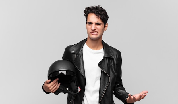 Giovane bell'uomo che sembra arrabbiato, infastidito e frustrato che urla wtf o cosa c'è che non va in te. concetto di motociclista