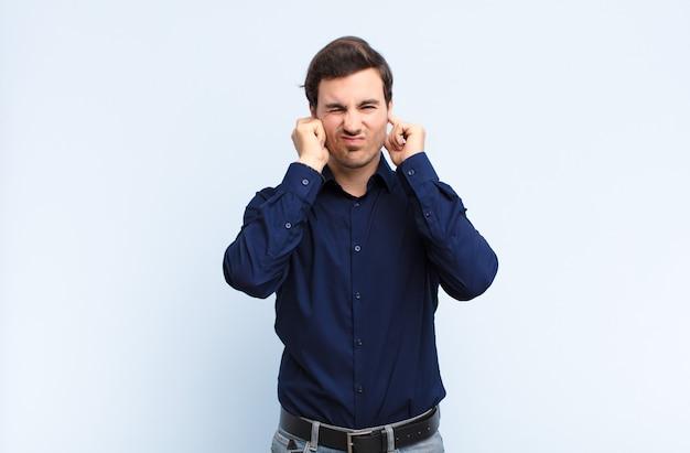 Giovane uomo bello che sembra arrabbiato, stressato e infastidito, coprendo entrambe le orecchie con un rumore assordante, suono o musica ad alto volume contro la parete blu