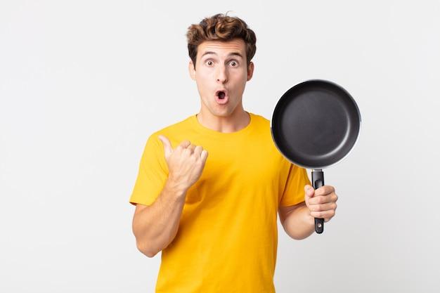Giovane bell'uomo che sembra stupito per l'incredulità e tiene in mano una padella da cuoco