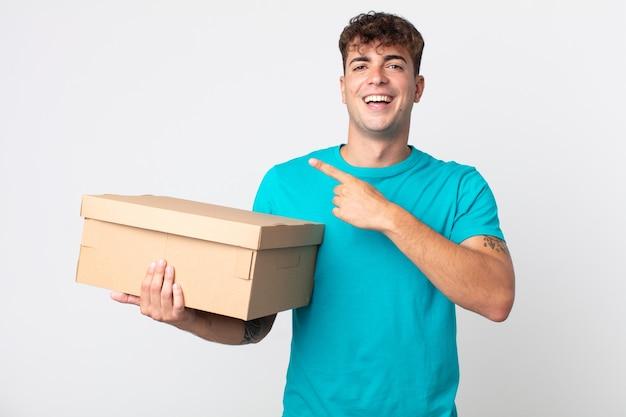 Giovane bell'uomo che sembra eccitato e sorpreso che indica il lato e tiene in mano una scatola di cartone