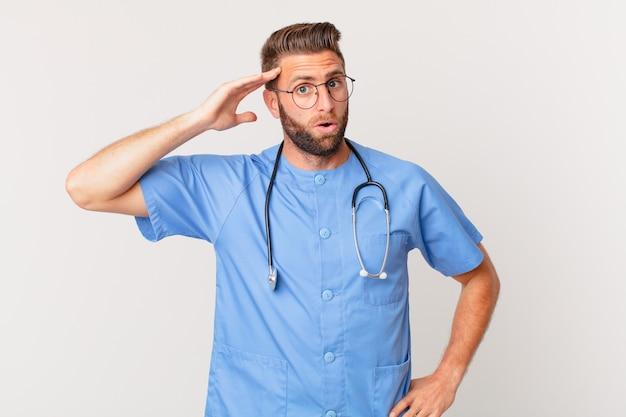 Giovane uomo bello che sembra felice, stupito e sorpreso. concetto di infermiera