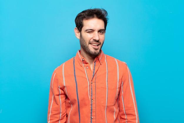 Giovane bell'uomo che sembra felice e amichevole, sorride e ti fa l'occhiolino con un atteggiamento positivo