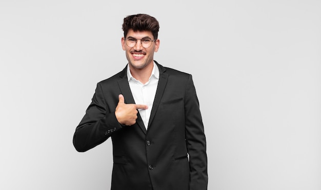 Giovane uomo bello che sembra felice, orgoglioso e sorpreso, indicando allegramente se stesso, sentendosi sicuro e alto