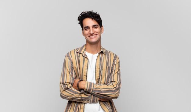 Giovane uomo bello che sembra un realizzatore felice, orgoglioso e soddisfatto che sorride con le braccia incrociate